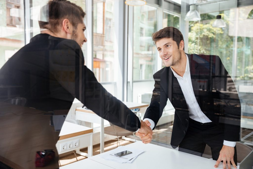 Two happy successful young businessmen standing and shaking hands on business meeting
